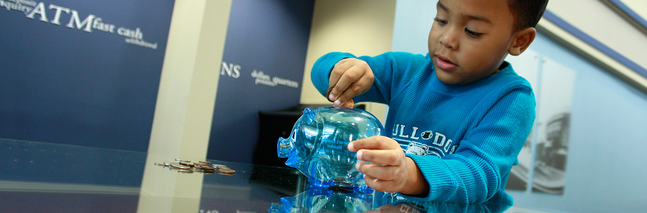 young boy putting coins in piggy bank