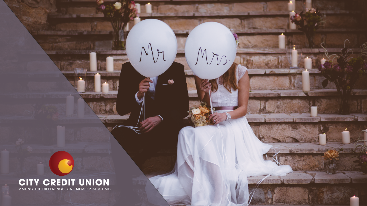 Newlyweds covering their faces with balloons labeled Mr. and Mrs.
