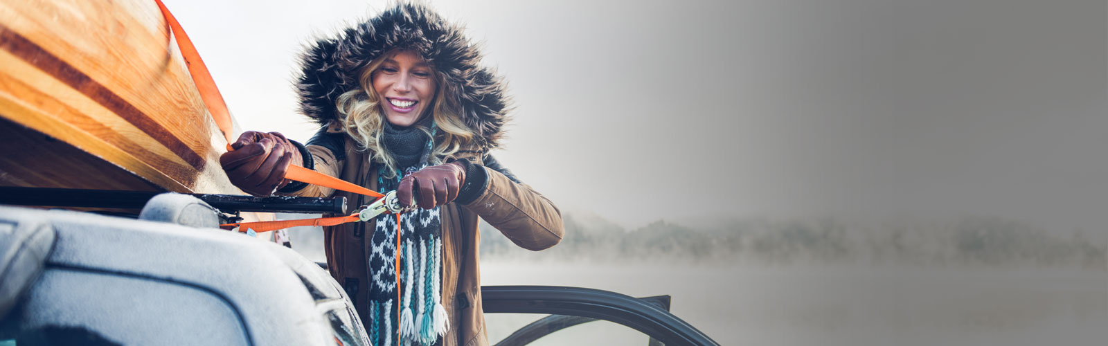woman in a parka cinching something to the top of her vehicle