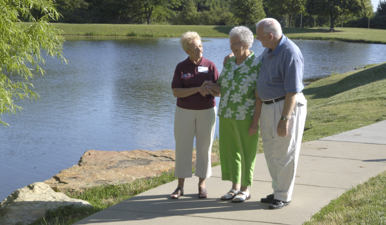 3 older people walking near a lake