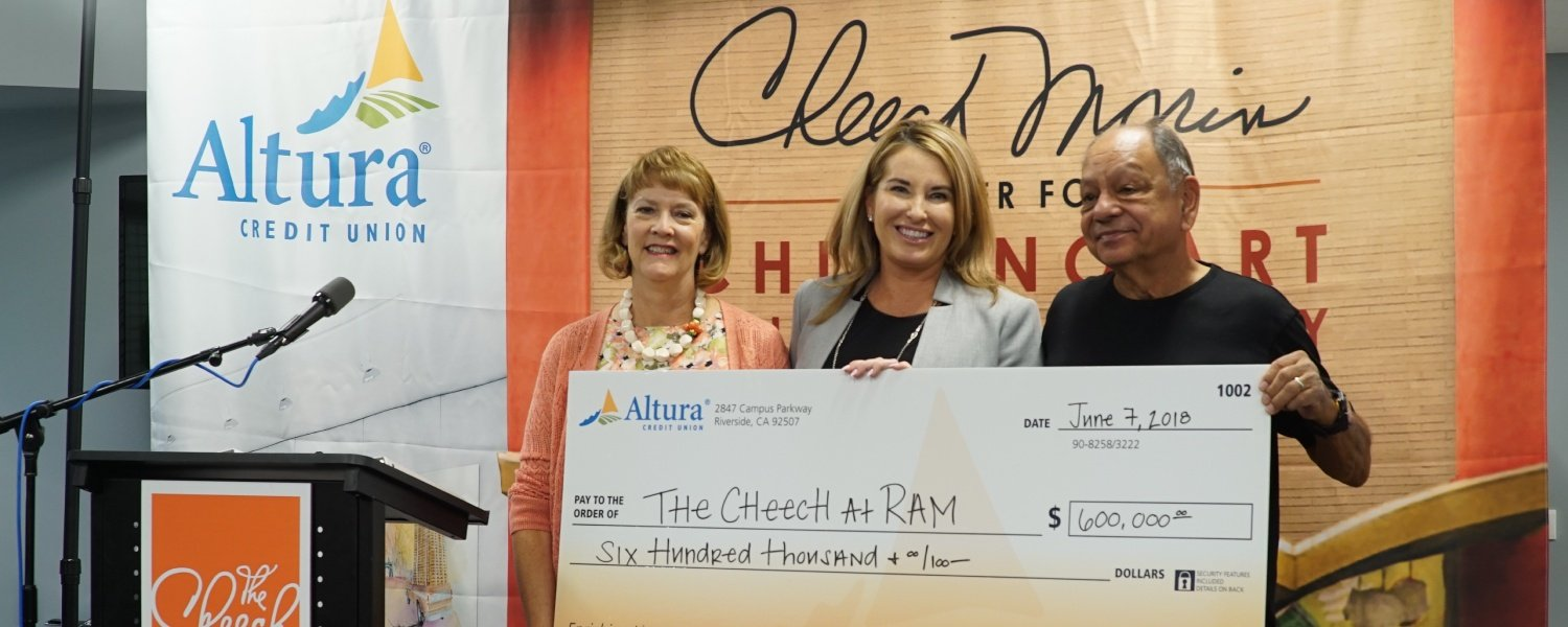 Altura CEO Jennifer Binkley and Cheech Marin hold check of 600,000 for Cheech Art Center